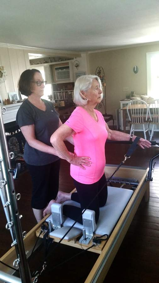 Yoga & Pilates for Health and Well-Being owner Karen DiRenzo works with a client.   Photo courtesy of Sarah Wadle
