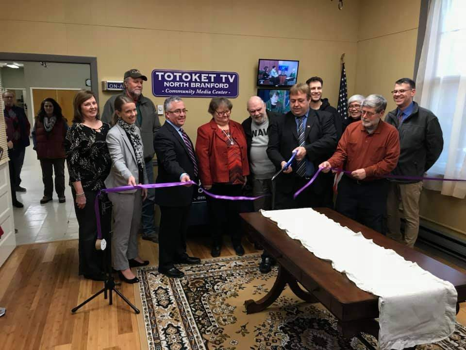 On Jan. 25, Local and state town leaders and members of the board of Totoket TV look on as Station Manager Walter Mann cuts the ribbon on the new home of North Branford's community access television station.  Pam Johnson/The Sound