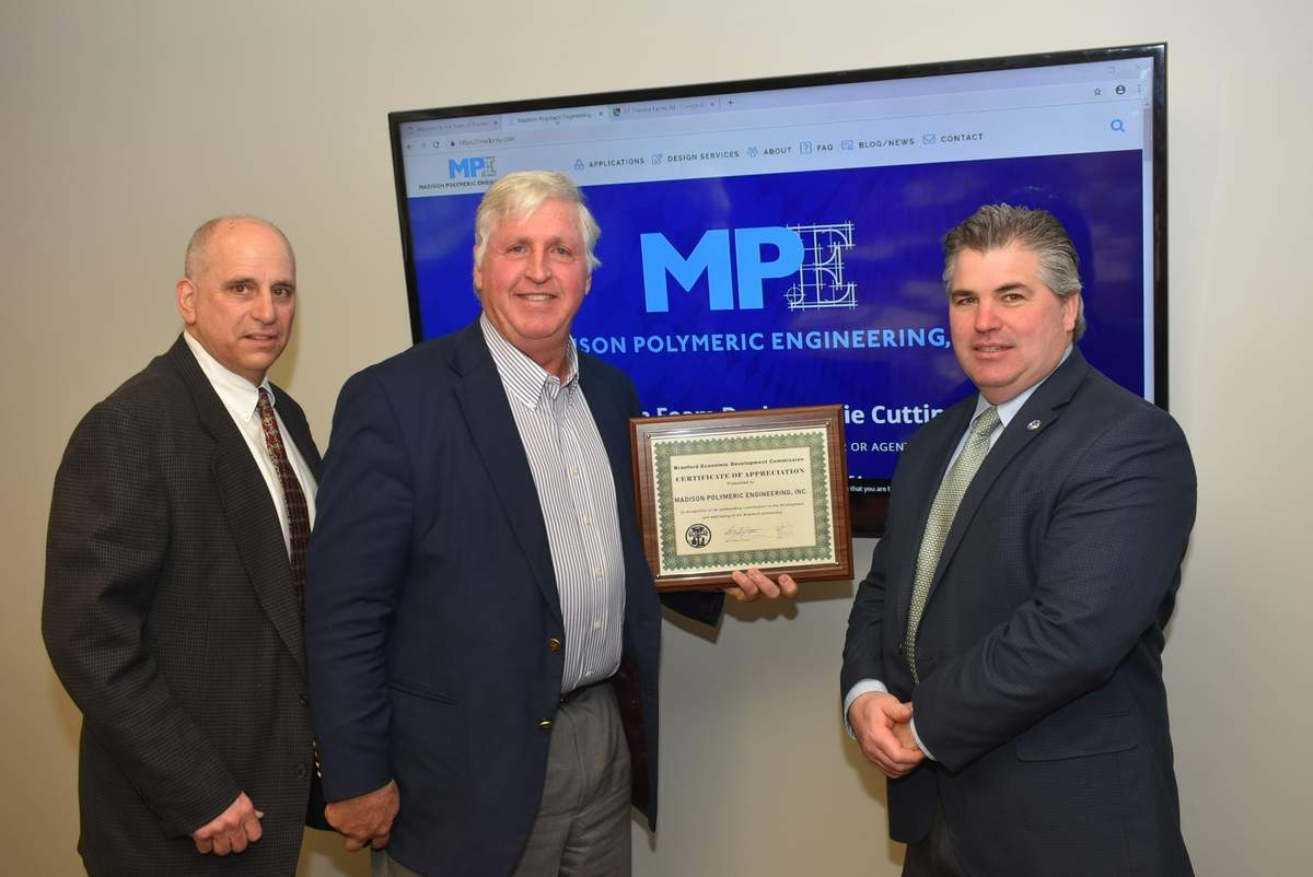 Madison Polymeric Engineering President and CEO Walter L. Maguire, Jr., accepts the Business Recognition Award from Branford Economic Development Commission Chair Perry Maresca (left) and First Selectman Jamie Cosgrove. Photo by Bill O'Brien