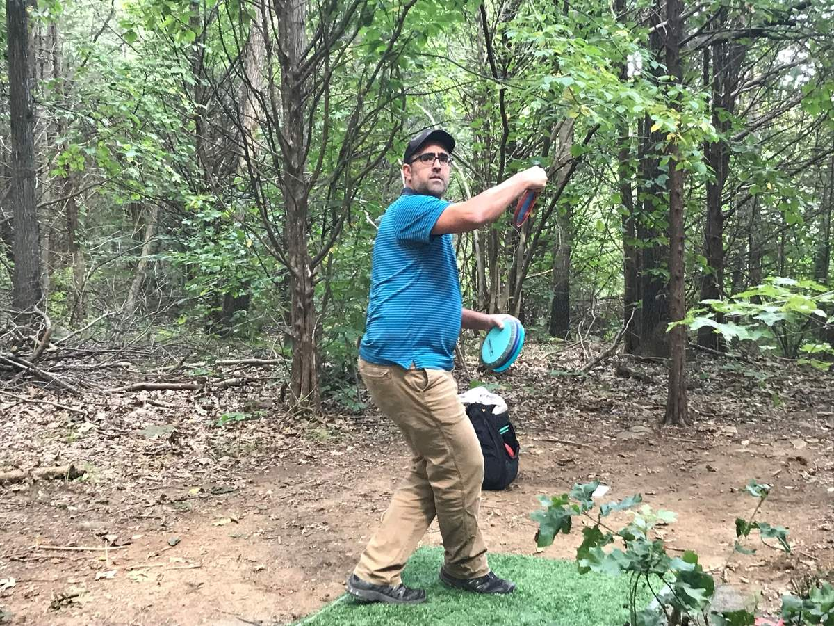 Volunteer course designer and semi-pro player Craig Smolin takes a spin from the first tee at Guilford's new Rick B. Maynard Disc Golf Course at Bittner Park.   Photo by Pam Johnson/Guilford Courier