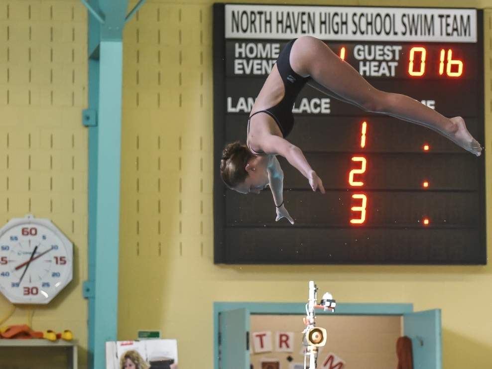 Senior Ava Santacroce broke her own school record for diving by scoring 243.60 points during Indians' 94-84 loss to Cheshire last week. North Haven came back to get a 102-81 win against Hand to improve to 7-1 this year. File photo by Kelley Fryer/The Courier