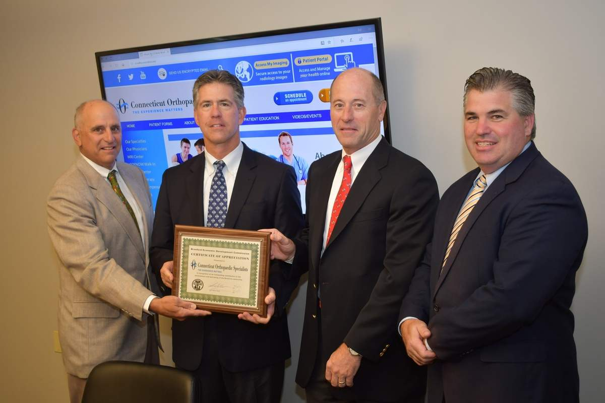 Branford Economic Development Commission Chairman Perry Maresca (left) and First Selectman James Cosgrove (right) present the Business Recognition Award to Dr. Patrick Ruwe and Dr. Jack Kelley of Connecticut Orthopaedic Specialists. Photo by Bill O'Brien