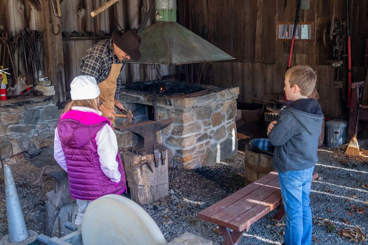 Harvest Home celebrated AmericaþÄôs Wooden Age at Bushnell Farm in Old Saybrook on Saturday, November 2, 2019. Farm volunteers and visiting artisans showed families demos dealing with wood and the farm. Guests could also press Cider, and visit the Wigwam and the BlacksmithþÄôs Forge. Livinia Osinski and Emmet Kelly watch as new Blacksmith Steve Sarnoski makes a coat hook at the Forge. Photo by Meglin Bodner/Harbor News