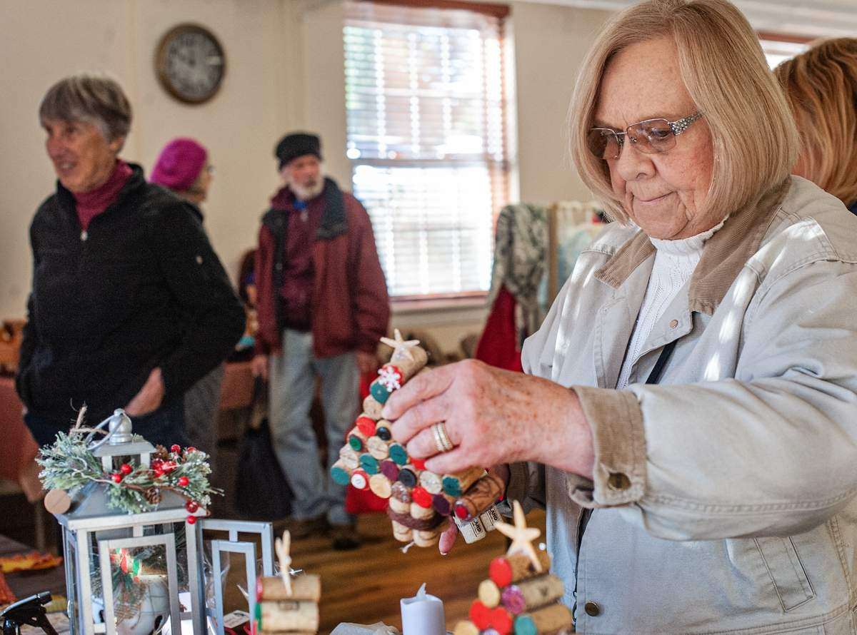 The WomenþÄôs Fellowship of the North Haven Congregational Church held its annual New England Fair on Saturday, November 2nd. The fair included handcrafted items, a yarn boutique, jewelry, accessories, kitchenware, cookies and baked goods, and items for Christmas gift giving.   Teri Rafter looks over a hand crafted Christmas tree made from wine corks.  Photo by Susan Lambert/The Courier