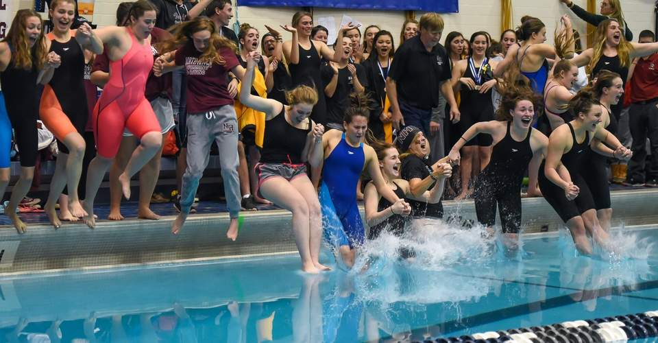 North Haven's athletes and coaches take a celebratory leap into the pool following a first-place finish at the Class M State Championship. The Indians scored a robust total of 622 points to bring the title back to North Haven. Photo by Kelley Fryer/The Courier