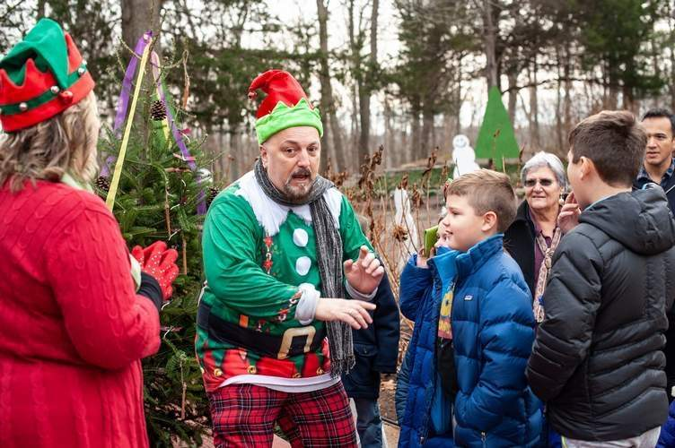 Part of the fun for all is interacting with the elves at the Magical Elf House. Shown here in 2018, house tour elf Mark Minotti tries to help kids figure out the password to enter the Magical Elf House. This year the house is popping up in Branford Dec. 14 and Dec. 15.  File Photo by Susan Lambert/The Sound