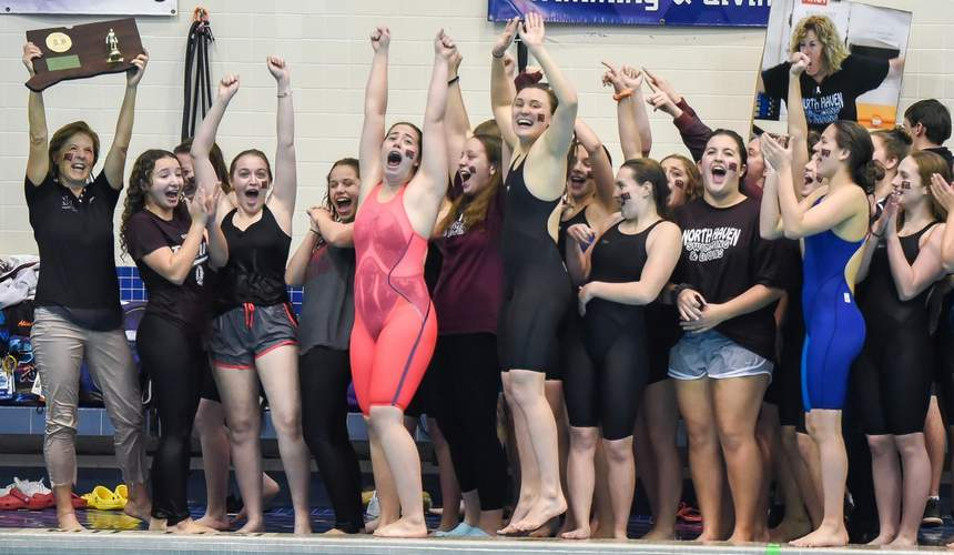 Head Coach Martha Phelan hoists the trophy after the North Haven girls' swimming and diving squad captured its first state title in program history by finishing in first place at the Class M State Championship. File photo by Kelley Fryer/The Courier