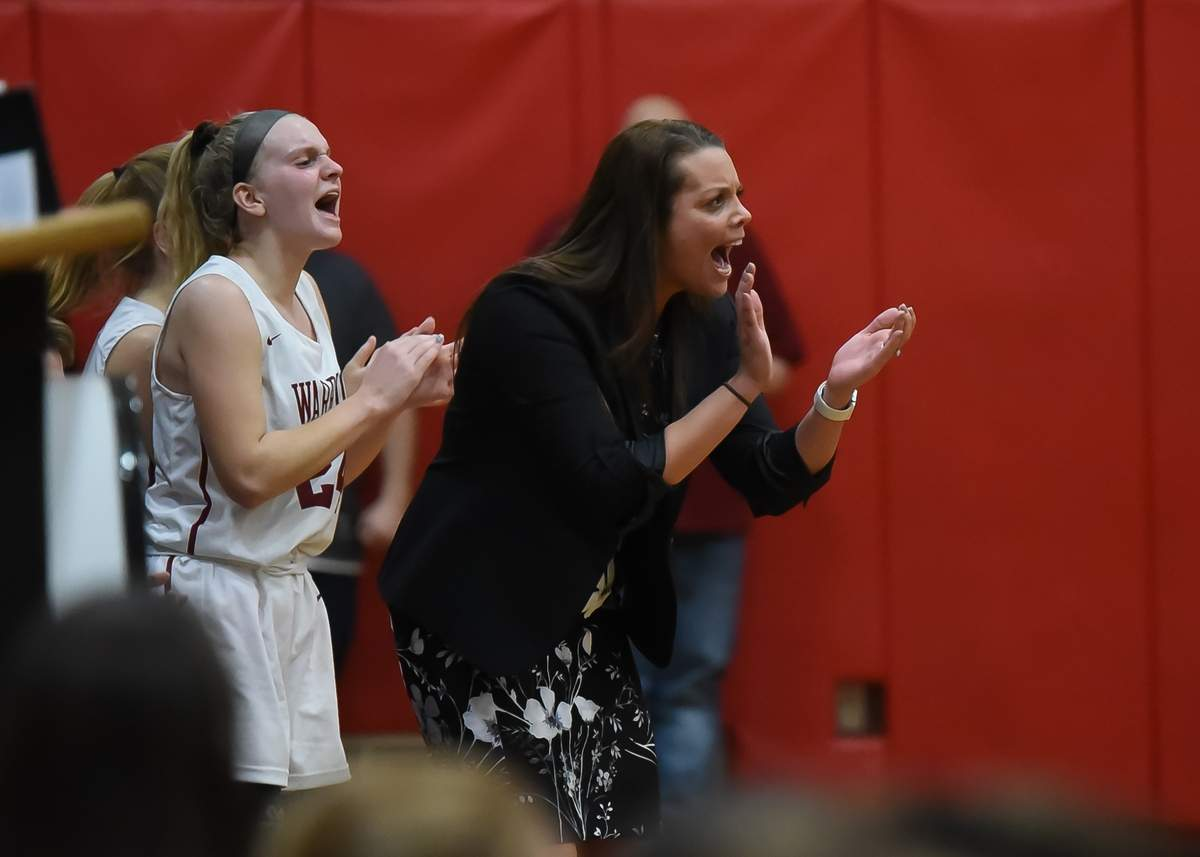 Elizabeth Cap  (24) and Head Coach Jaimie Toto cheer on the team. Photo by Kelley Fryer/The Courier