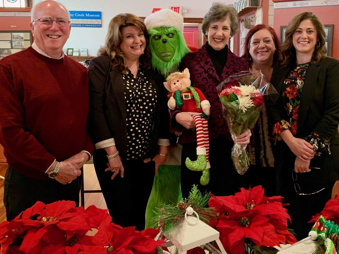 Bob Babcock of the Stony Creek Museum (left) and Shoreline Chamber of Commerce Executive Director Sheri Cote (right) accept donations from Magical Elf House designer Ramona Eldridge of Design House Interiors, The Grinch (Nick Giordano), homeowner Julie Broom, and designer Jennifer Napolitano of Design House Interiors. Photo courtesy of Jill Dechello
