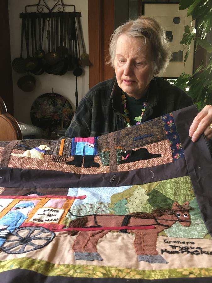 Established clay artist Gloria Elliott has also mastered other art forms, including quilting, which she uses to tell her family's story. In the foreground, a panel depicts her father, a Norwegian emigré who found a job delivering milk by horse. Photo by Aviva Luria/The Courier