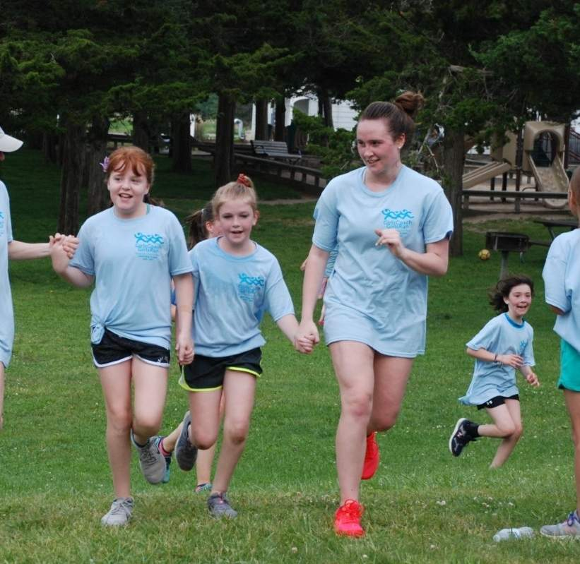 Shown here helping 4th grade girls cross the finish line at the 2019 Girls Coach, Girls Run (GCGR) 5K Fun Run, Tara Henry (right) has experienced the empowerment of the Women & Family Life Center (WFLC) program in all of its stages—as a 4th grade participant, an 8th grade coach-in-training, and high school head coach. Photo courtesy of the Women & Family Life Center