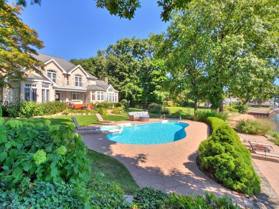 A manicured lawn surrounds the pool and leads down to Branford Harbor.