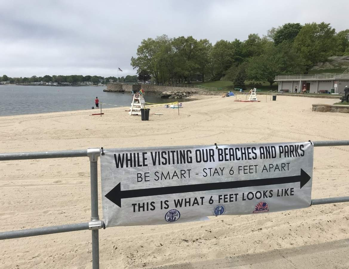 Branford Point, a Town beach, opened early for the season on May 25; with the public expected to do its part in following current COVID-19 safety practices. To help with social distancing, signs posted around the beach, with arrows spanning the actual six-foot distance requirement, help beach-goers visualize what the safe spacing should look like.  Pam Johnson/The Sound