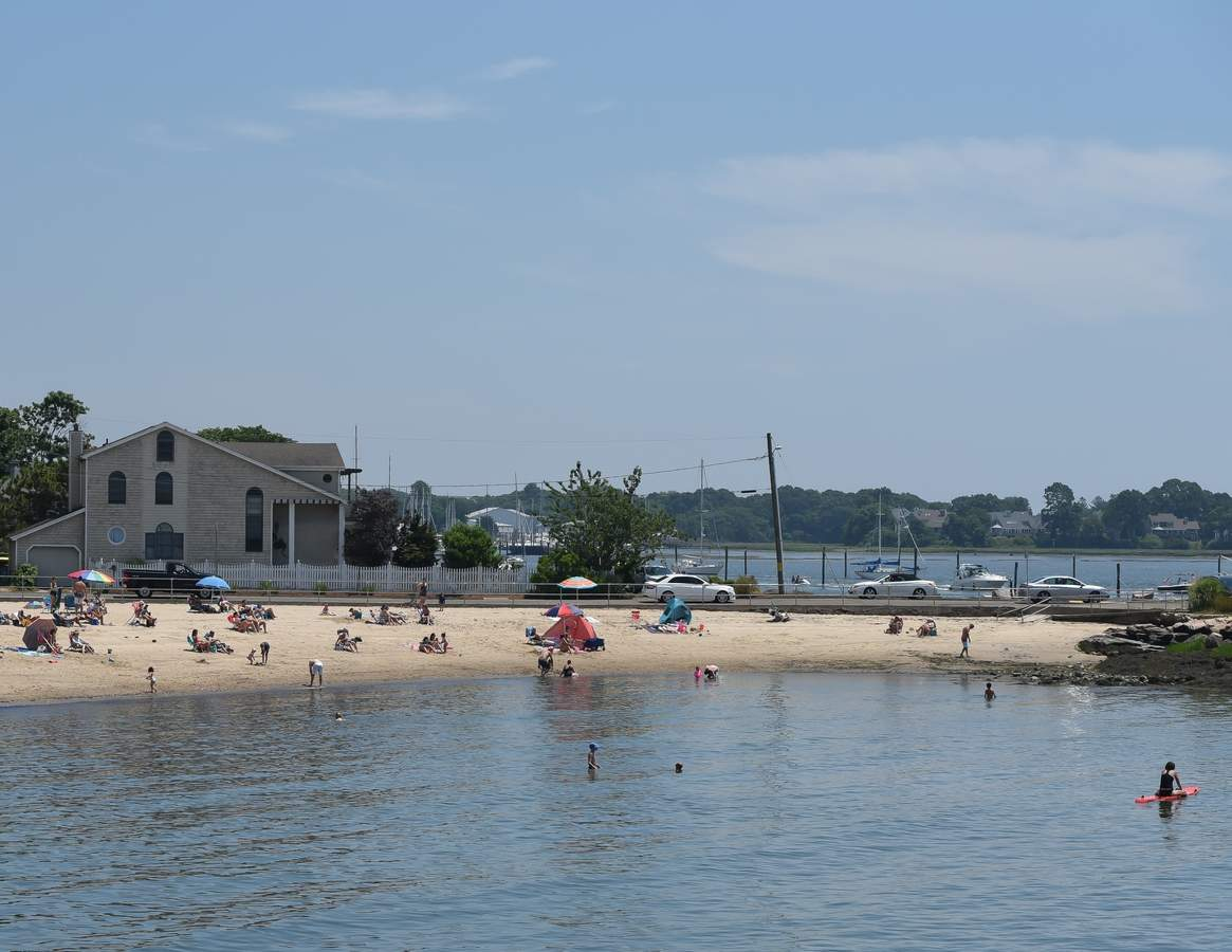 A sunny warm summer Sunday at Branford Point had people swimming, sunbathing  and boating. Photo by Kelley Fryer/The Sound