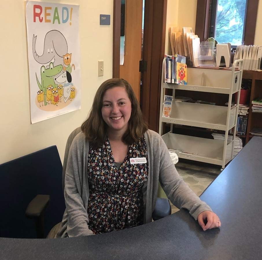Behind the desk at the Essex Library, Child and Teen Librarian Christina Carpino is working to assist patrons despite the challenges of the COVID pandemic.  Photo courtesy of Christina Carpino