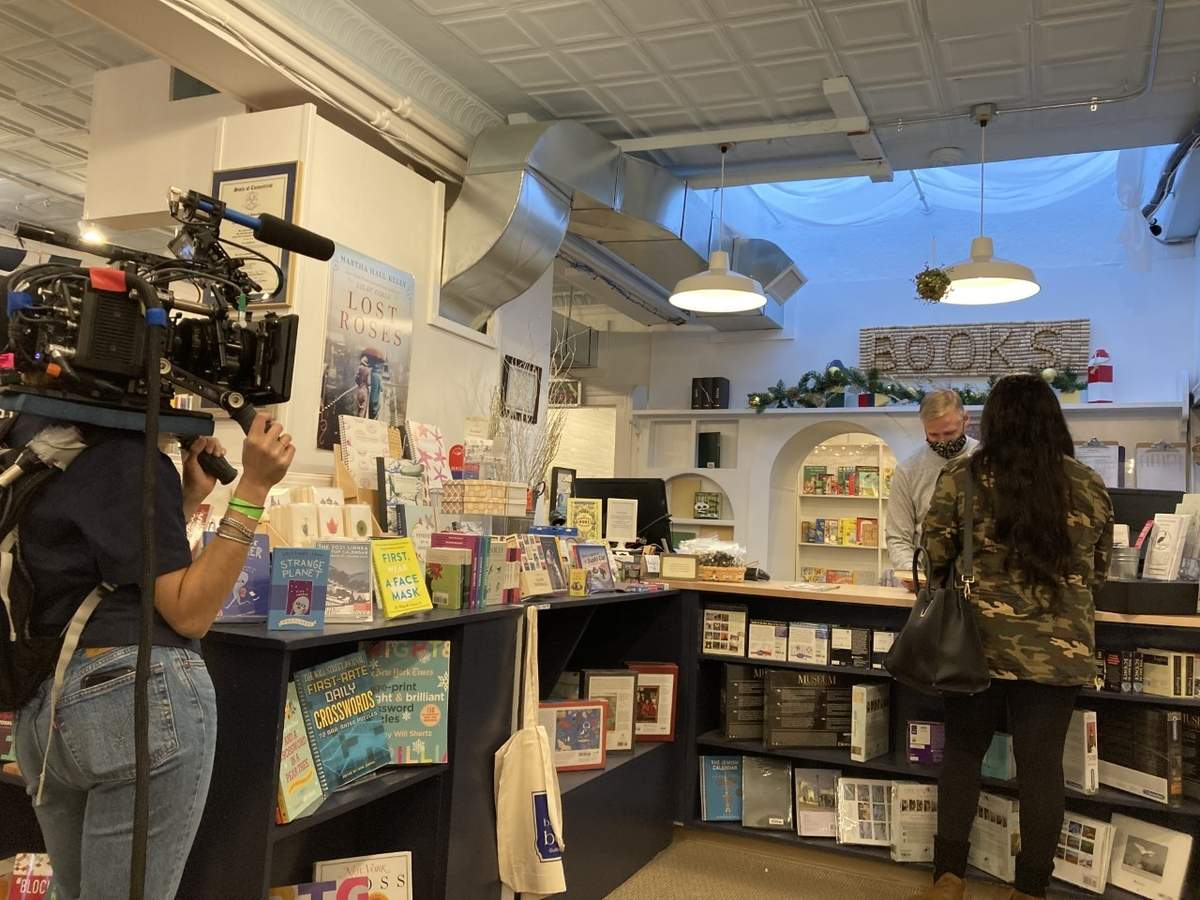Breakwater Books co-owner Richard Parent faces actress Donna Dupervil (right) and director Karina Silva (left) during filming for an international American Express ad campaign focusing on small businesses. Photo courtesy of Breakwater Books
