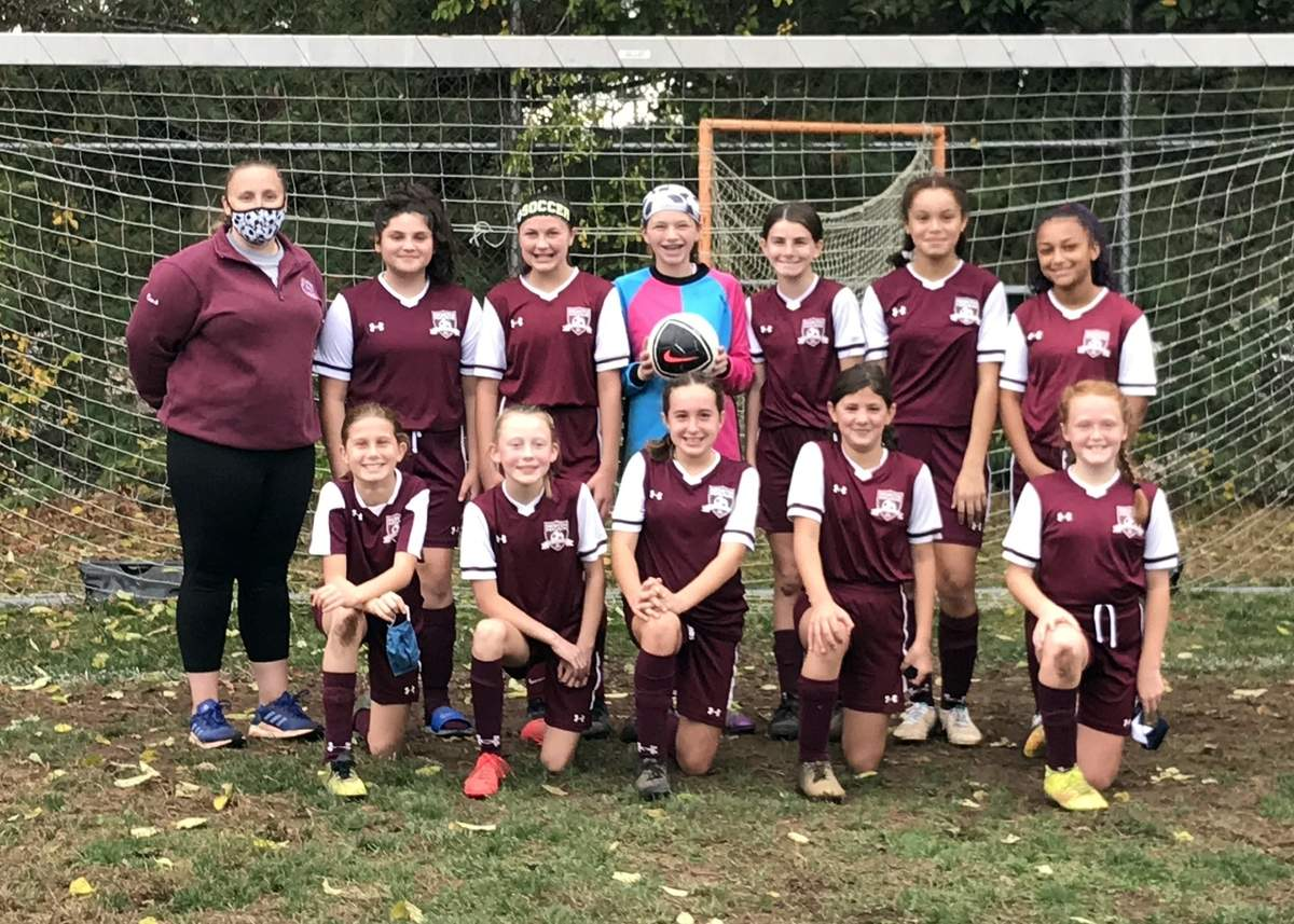 North Haven's U-12 comp girls' soccer squad went 4-0-1 on its way to winning a South Central District division title last fall. Pictured are (front) Estelle Hammarlund, Marcy Funke, Ava Tarasuk, Lillianna Osborne, and Maddie de Lencastre with (back) Head Coach Jen Merck, Kayden Goss, Lia Calderon, Addison Whitcomb, Peyton Harkins, Maya Thompson, and Leila Sweet. Missing from the photo is Assistant Coach Erika Fronte. Photo courtesy of Chris Kirby