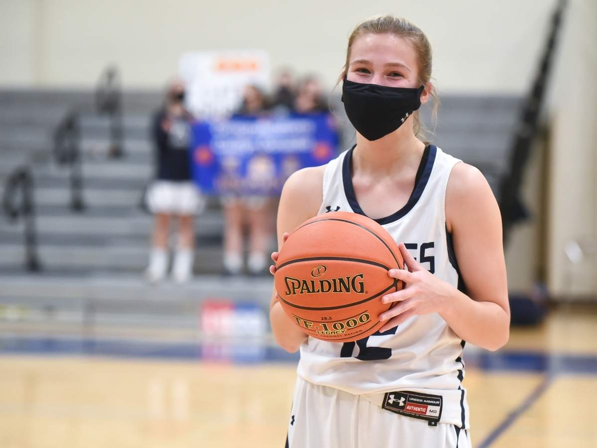 Senior captain Catie Donadio was presented with the game ball after scoring her 1,000th career point during Morgan's 47-32 home victory against North Branford on Feb. 16. Donadio had 16 points with 10 steals, five assists, and two blocks in the contest.  Photo by Kelley Fryer/Harbor News