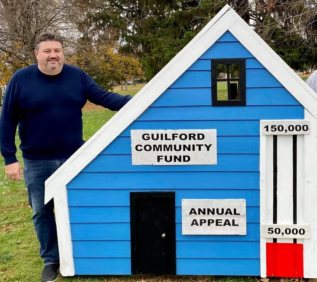 Adrian Price, president of non-profit Guilford Community Fund (GCF), stands at the familiar saltbox house at the corner of Whitfield and Boston streets, reminding all Guilford neighbors it's time to support GCF's annual appeal. Photo courtesy of the Guilford Community Fund