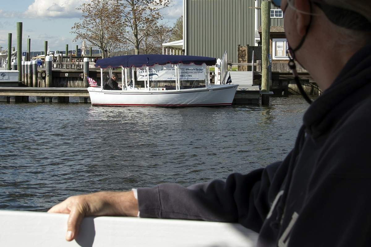 Paul Ahern looks over at an electric boat on display while taking the ferry to Safe Harbor Essex Island for the fifth CT Spring Boat Show on Friday April 30th.  Half of the gate proceeds benefitted Sails Up 4 Cancer.   Wesley Bunnell / Valley Courier