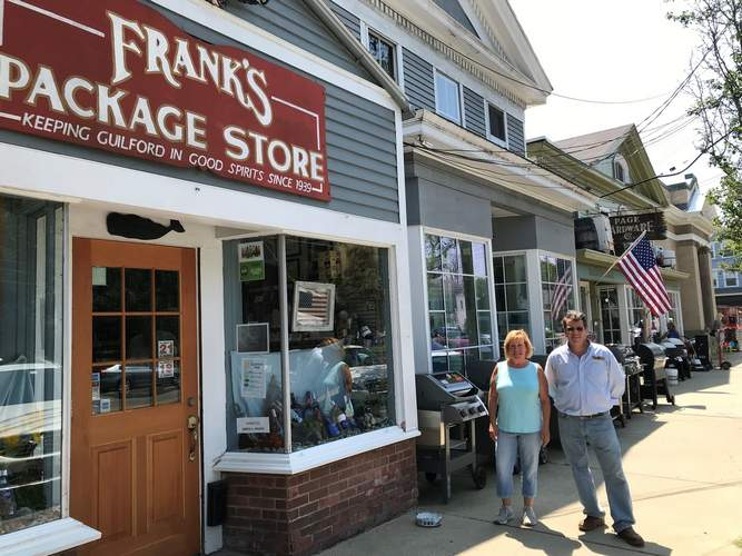 Kirsta Ifkovic and Andrew Page represent the third generation of ownership of Frank's Package Store and Page Hardware Co., respectively; both stores are celebrating their 80th year at the south end of the Guilford Green. Photo courtesy of Andrew Page
