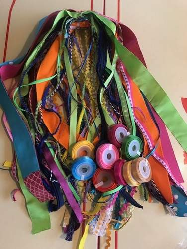 Using donated sourced materials like these colorful ribbons, Amy Peters is helping to piece together artful fabric bags. Photo courtesy of Amy Peters