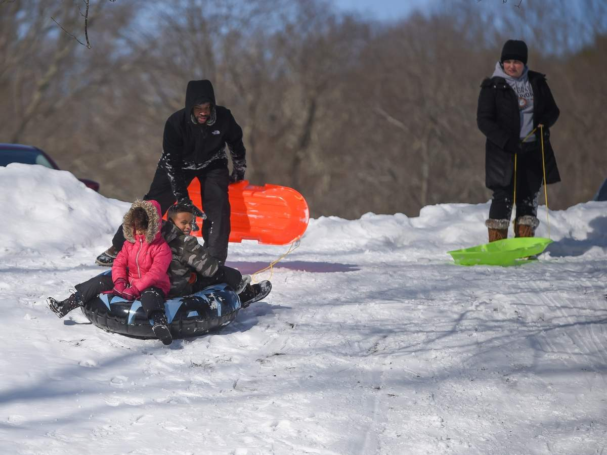 Fresh snowy powder brought out the sledders on Saturday morning to the hill behind Green Acres Elementary School. The Nesmith famiy got ready to sled down the hill. Curtis  gave Quennell and Layla a push down the hill, mom Ashley watched them go.  Photo by Kelley Fryer/The Courier