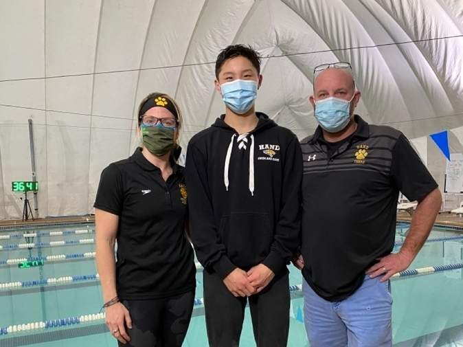 The athletes on the Hand boys' swimming and diving squad have been turning in plenty of proud performances during the 2021 campaign, including a school-record performance from freshmen Elliot Lee in the 100 butterfly. Pictured are Tigers' Head Coach Christina Forristall with Lee and Assistant Coach Scott Butler. Photo courtesy of Christina Forristall