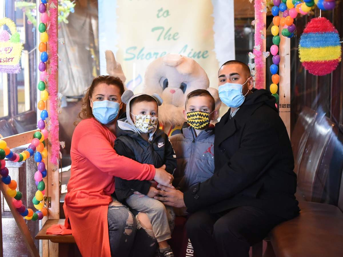 The Shore Line Trolley Museum held the annual, (Covid Modified) þÄúRide with the Easter Bunny!þÄù on Saturday from 11am - 4pm with limited tickets needed to be purchased in advance.  The Easter Bunny sat behind a plexiglass barrier with a bench in front for families to take photos. The trolley carþÄôs touch points were cleaned between each family, as was the trolley cars after each group. Gina (Rao) Flores,  Zachary, Andrew, and Zachary Senior Flores posed for a photo in front of the Easter Bunny on the Trolley Car.  Photo by Kelley Fryer/The Courier