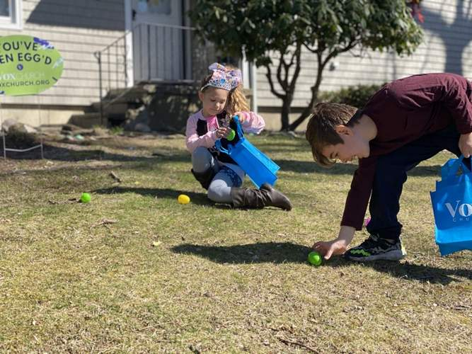 Wyatt and Presley Henriques search for eggs provided by one of the portable Easter egg hunt kits Vox Church delivered to congregants. Photo courtesy of Dave Bruno